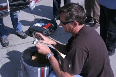 """Doug Holgate checks the 1/2"""" thick optical glass that covers the front of the nose mount. The glass was pitted and needed to be replaced at the last minute."""