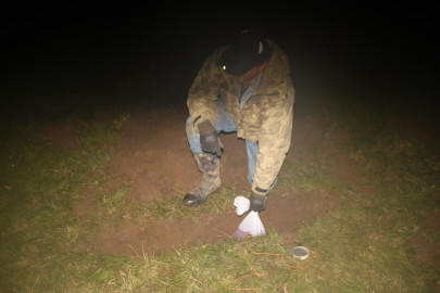 Placing the bag containing the gasoline in the hole. The powder charge with electrical wiring can be seen on the ground.