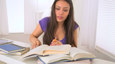 Young woman doing homework and talking on smart phone