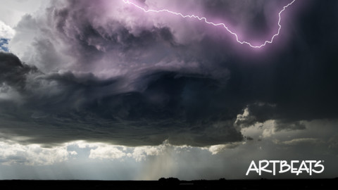 EST104: TIme-lapse swirling dark gray supercell cloud with lightning and rain over a prairie landscape.